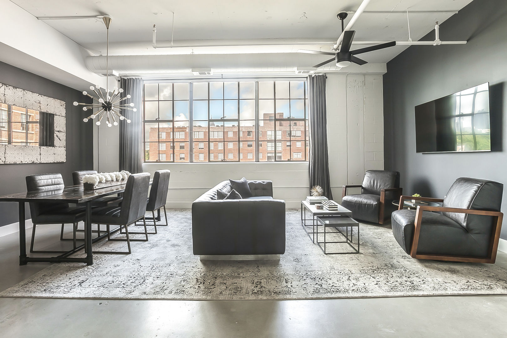 Living and dining area of this Ponce Market Apartment with ample seating and a wall-mounted TV.