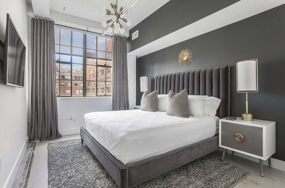 Bedroom of this Ponce Market Apartment with a large bed and twin nightstands.