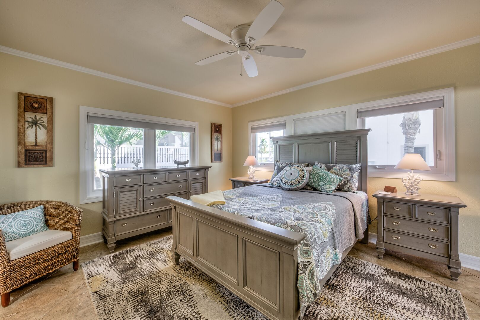 Guest bedroom with queen bed and chair in our Fort Myers cottage