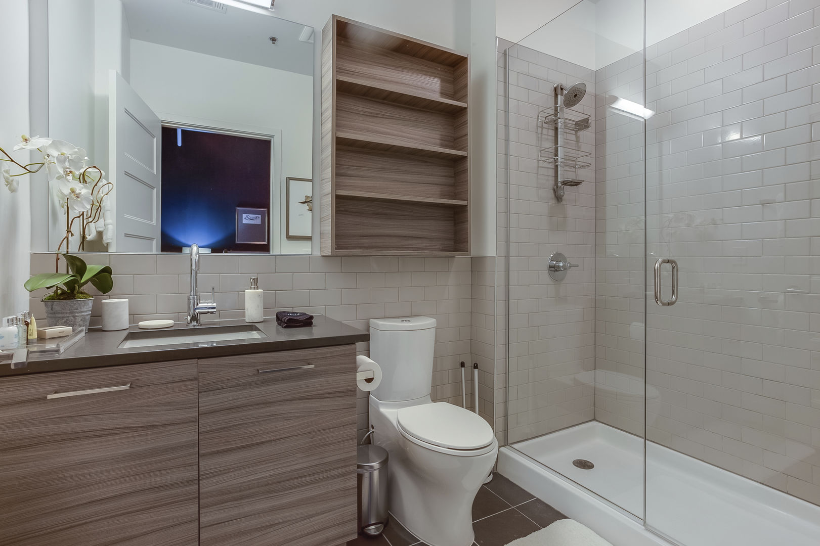 Master Bathroom of this Apartment Near Ponce City Market with vanity sink, toilet, and walk-in shower.