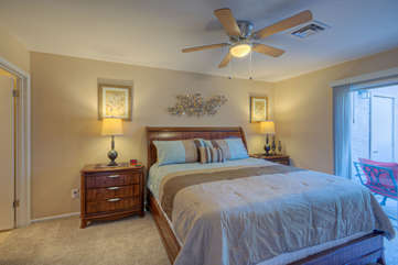 Primary Suite One has a king bed, doors to patio, a walk-in closet, ceiling fan and TV