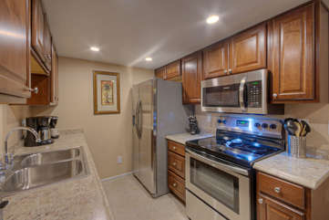 Galley kitchen is well lit and has shiny new appliances and other recent upgrades