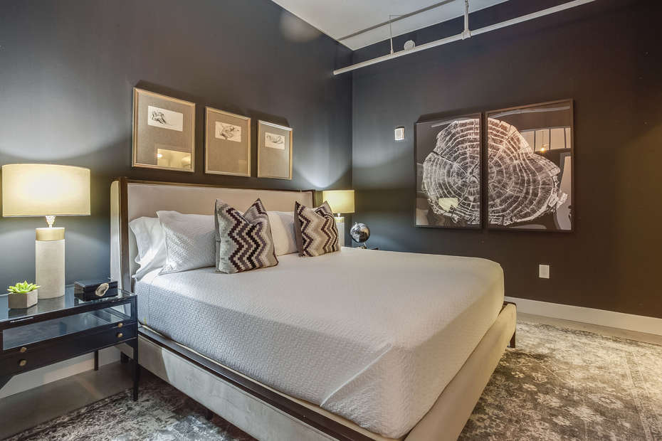 Master Bedroom of this Apartment Near Ponce City Market, with a large bed, two nightstands, and decorative wall-hangings.