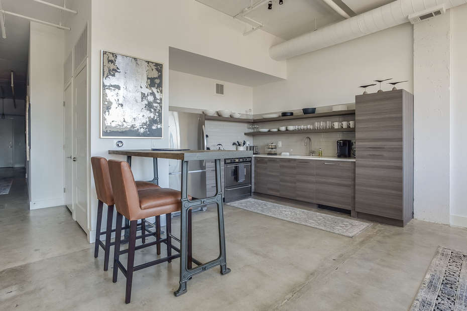 Kitchen of this Apartment Near Ponce City Market with modern appliances and small table with two chairs.