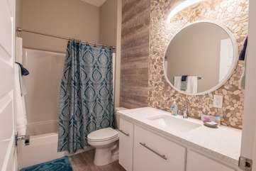 Awesome downstairs full guest bathroom with both the trendy stone wall backdrop and blue, beachy-feel shower