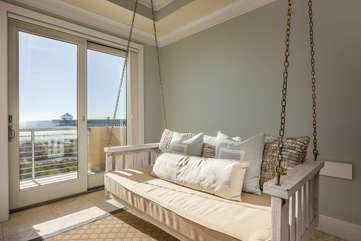 spacious living room with swings overlooking private balcony with beachfront views