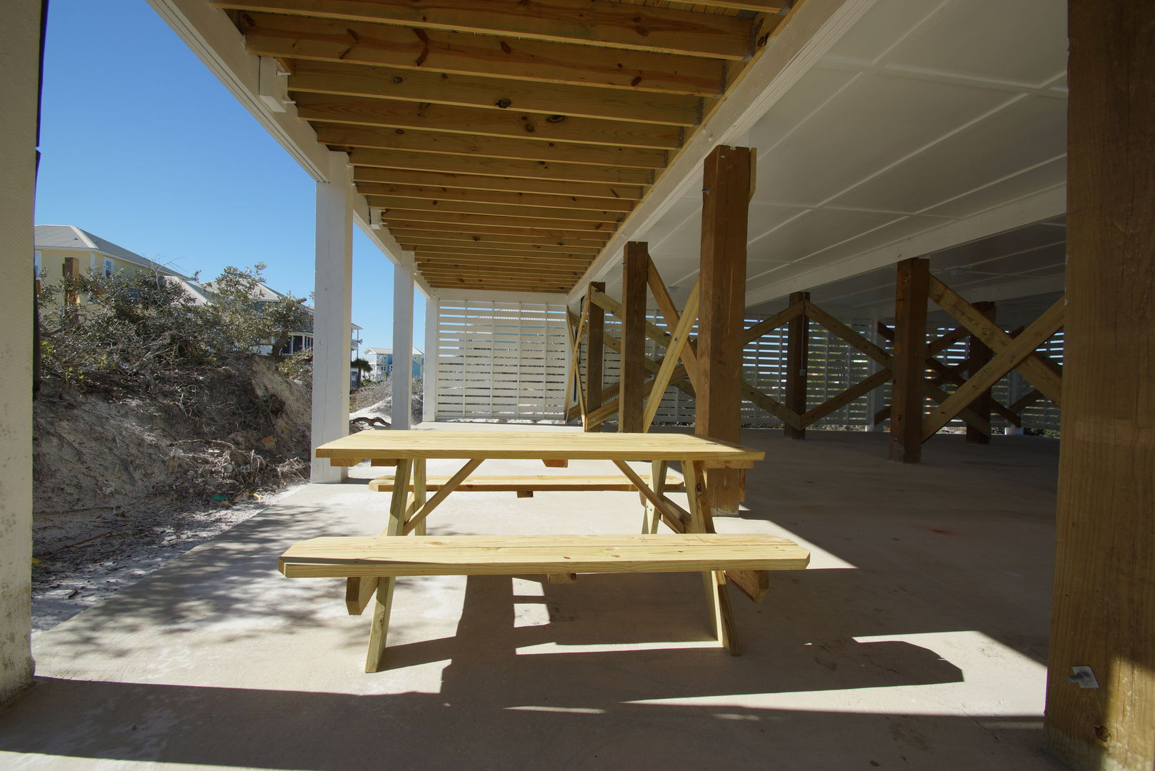 Covered carport with picnic table for dining.