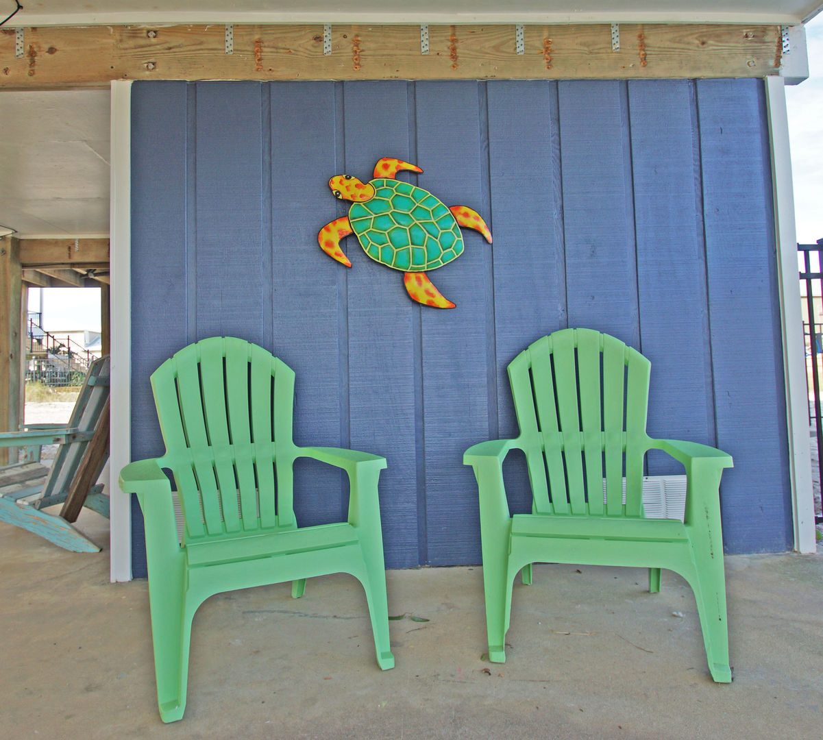 Two Outdoor Chairs in the Shaded Area Under Home.