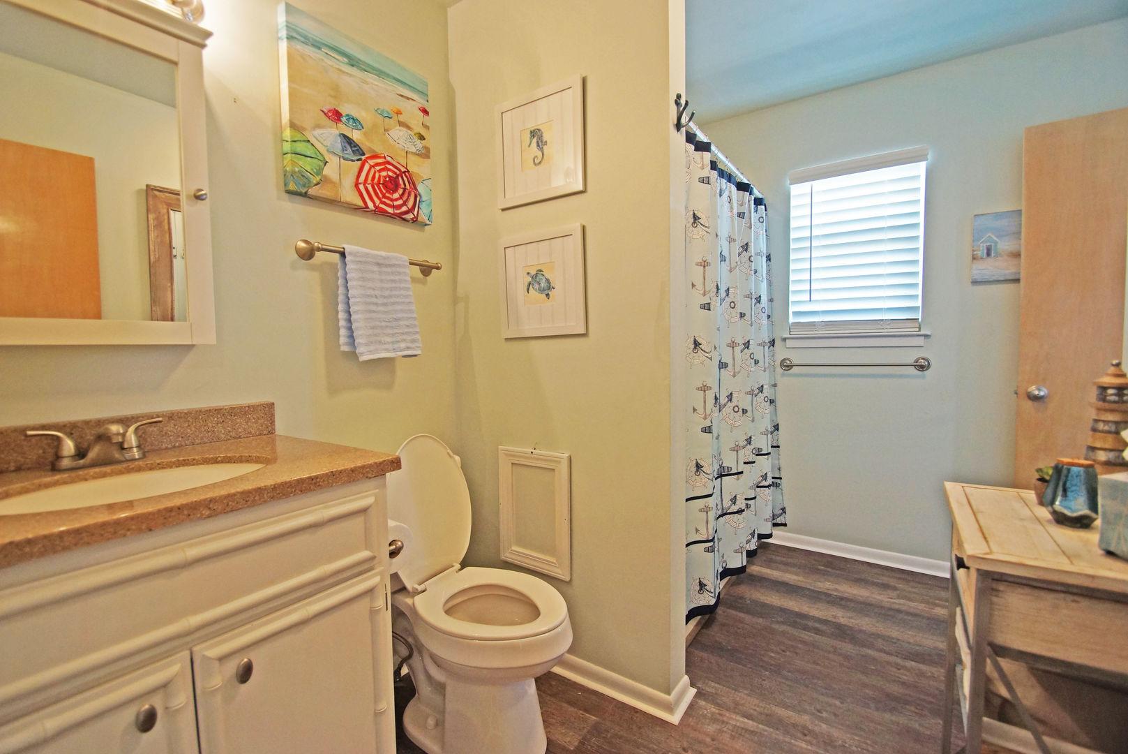 Single Vanity Sink, Shower, Mirror, and Toilet.