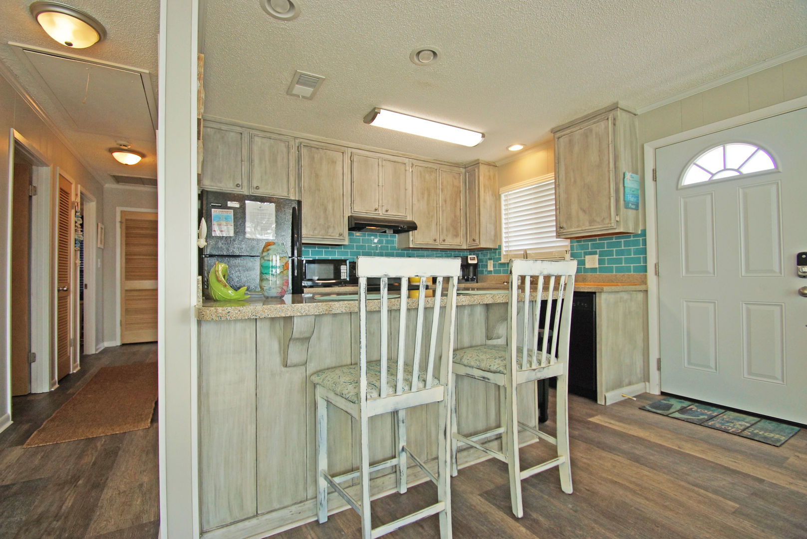 Kitchen Counter, Stools, Refrigerator, Microwave, and Coffee Maker.