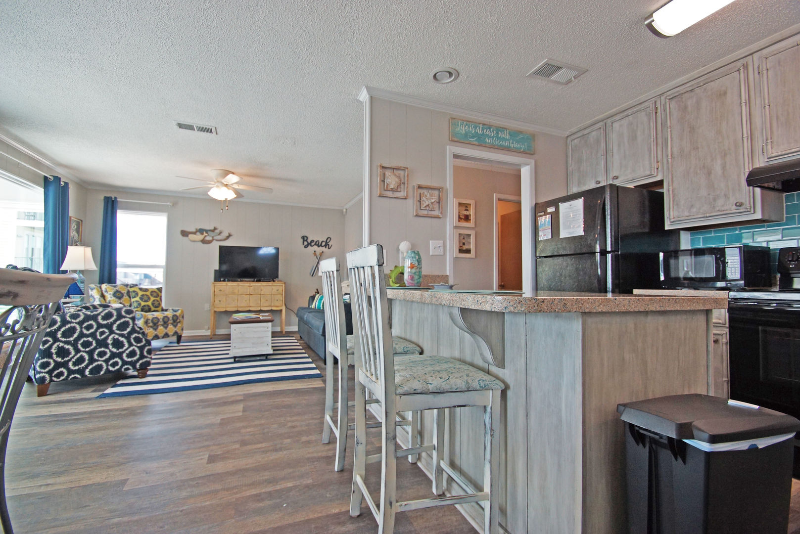 Kitchen Counter, Stools, Refrigerator, TV, and Arm Chairs.
