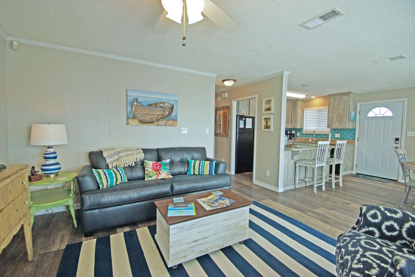 Sofa, Coffee Table, Kitchen Counter, Stools, and Ceiling Fan.
