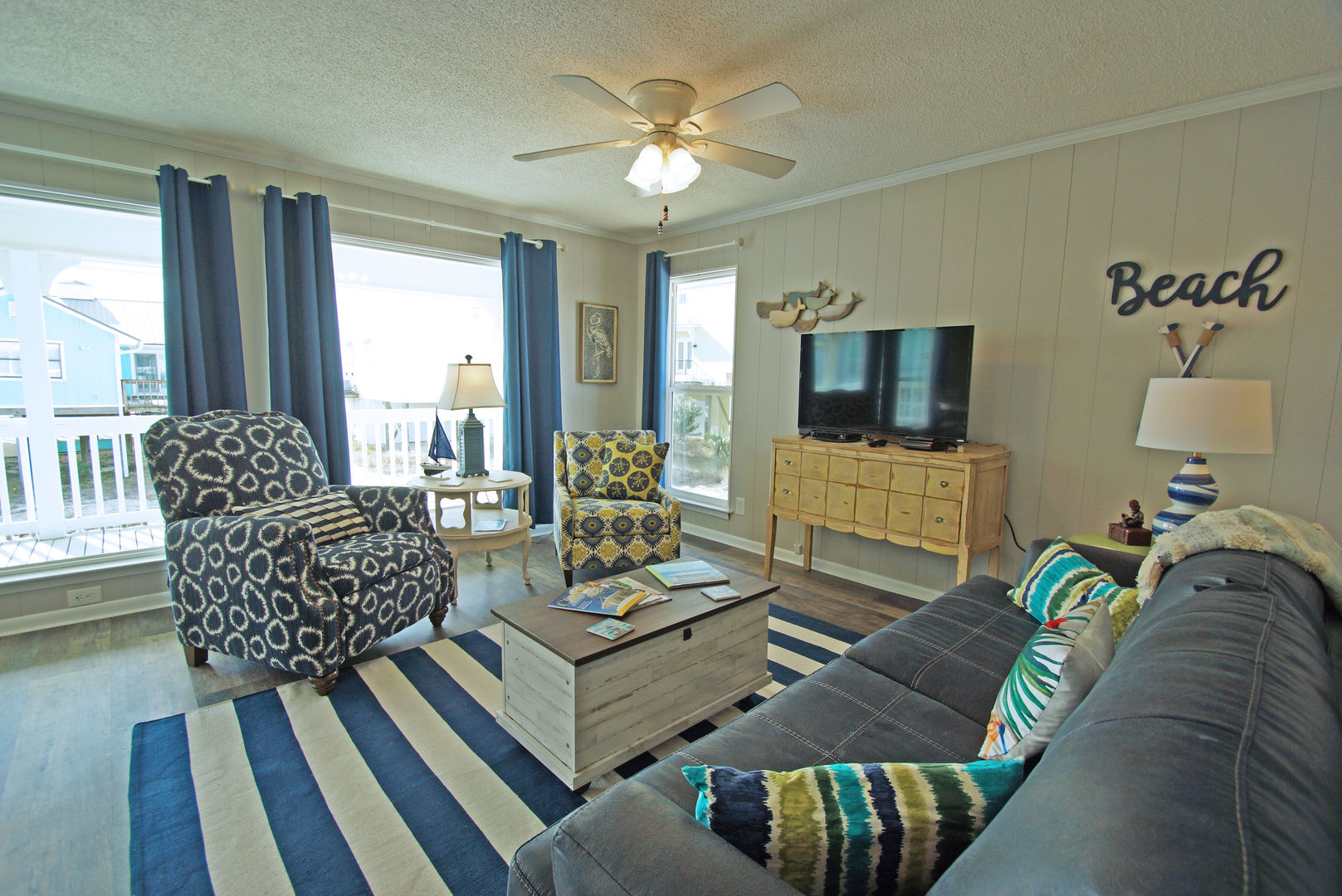 Arm Chairs, Side Table, Coffee Table, TV, Sofa, and Ceiling Fan.