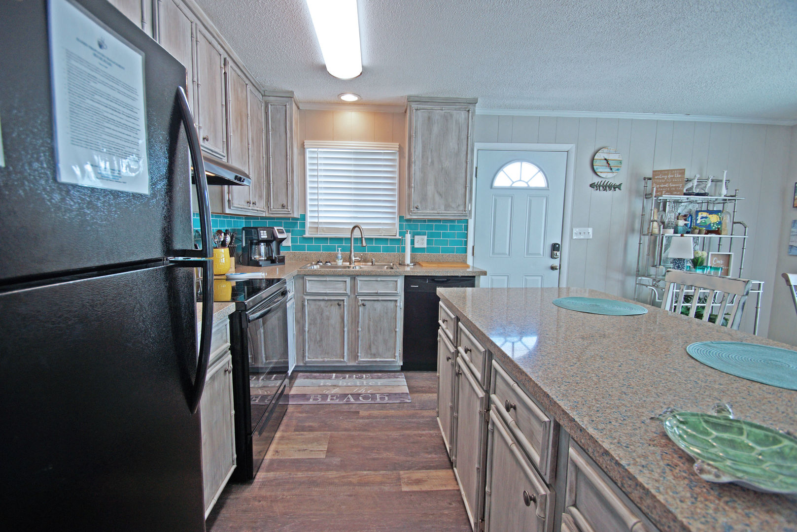 Kitchen with Counter, Refrigerator, Coffee Maker, Bookcase, and Chairs.