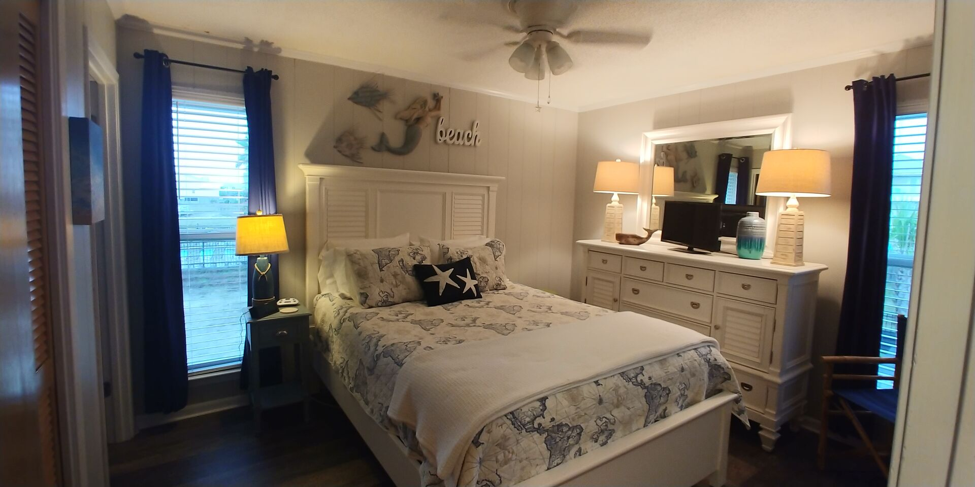 Large Bed, Drawer Dresser, Mirror, Lamps, and Ceiling Fan.