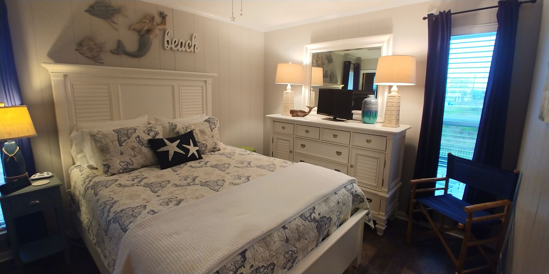 Large Bed, Drawer Dresser, Mirror, Lamps, and Chair.