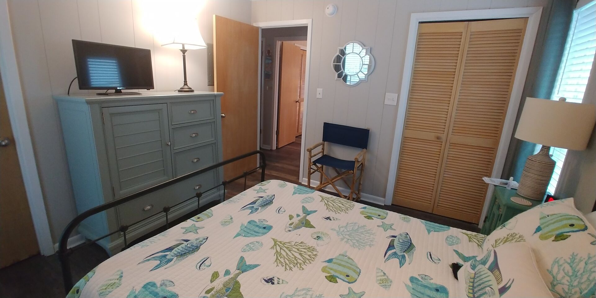 Large Bed, Dresser, Lamps, Chair, TV, and Closet Doors.