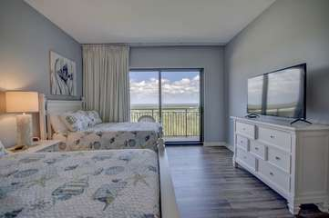 Guest bedroom with two full beds and large flat screen TV