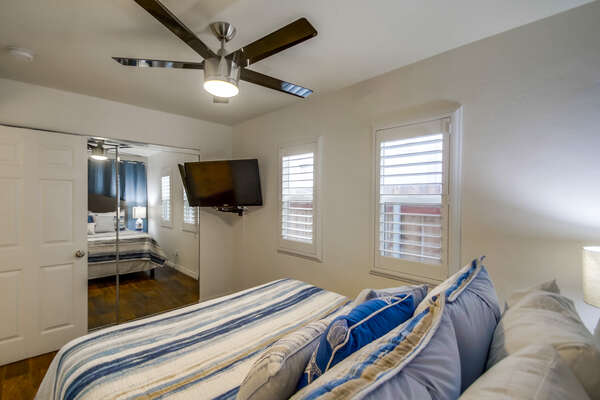 Bedroom with Large Bed, Closet Doors, TV, and Ceiling Fan.