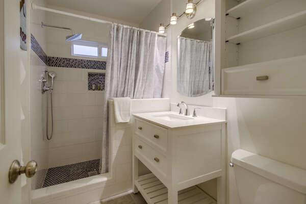 Single Sink Vanity, Shower, and Toilet.