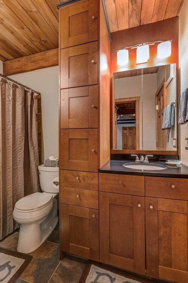 Plenty of storage in the bathroom, around a vanity sink and toilet.