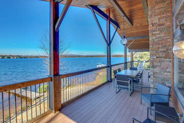 A picture of the lake taken from the back porch, with outdoor furniture and a view of the dock.