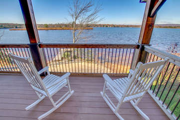 Two rocking chairs facing the lake on the porch of this Poconos rental by the lake.