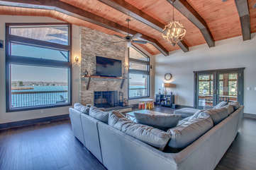 Great room with sectional couch, TV, fireplace, and large windows overlooking the lake.