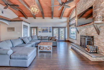 Living area with large sectional, coffee table, fireplace and TV.