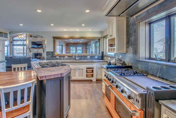 The large oven, island stove top, and sink of the kitchen in this Poconos rental by the lake.