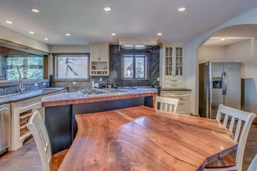 The unique wood table of the kitchen, with chairs around it, beside the kitchen island and sink in the background.