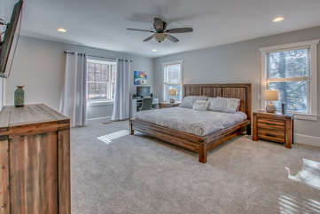 Master bedroom of this Poconos rental by the lake, with large bed, nightstand, computer desk, and a TV and dresser in front of the foot of the bed.