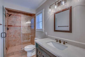 Master bathroom with walk in shower (and glass door), sink, and toilet.