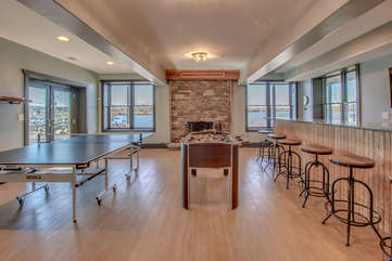 The game room with Foosball table, bar stools against the right wall, and ping pong table by the sliding glass door on the left. Fireplace in back.