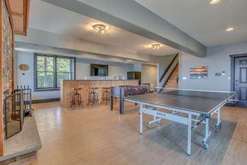 Ping pong table, Foosball table, and bar seating facing a TV of the game room on the lower floor.