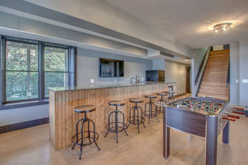 Bar seating, TV and Foosball table of game room.