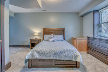 Large bed and nightstand of one of this rentals bedrooms.