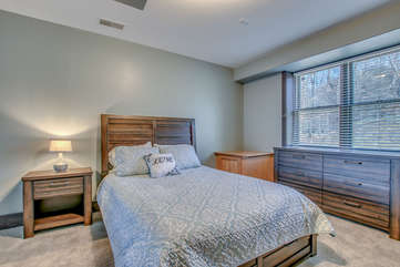 Angled picture of a large bed, nightstand with lamp, and large dresser.