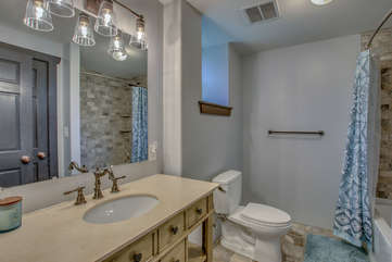 Sink with large mirror, toilet, and shower (with curtain open).