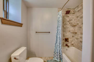 Bathroom with tiled shower with the curtain open and a toilet in the bottom left.