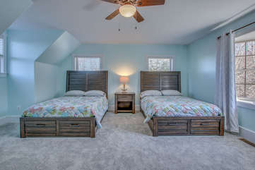 Two side-by-side beds with high headboards, with a nightstand and lamp between them.