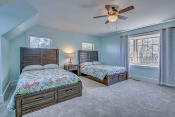 Two beds side by side in one of the bedrooms of this Poconos rental  by the lake, with a nightstand in between.