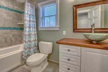 Bathroom with toilet, shower (with curtain open), mirror and bowl sink.