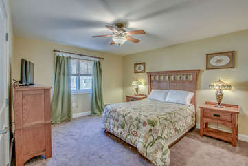 One Bed Bedroom with Two Nightstands, Dresser, TV, and Ceiling Fan.