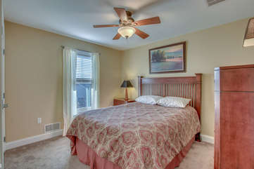 Bedroom with Large Bed, Dresser, Nightstand, and Ceiling Fan.