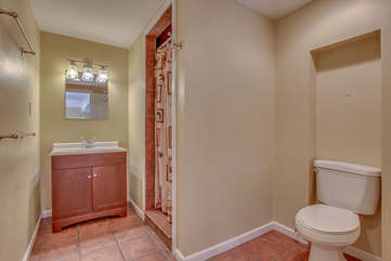 Picture of a Bathroom with Toilet, Sink, Mirror, and Shower.