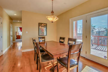 Dining Table with Chairs, Ceiling Lamp, and Double Balcony Doors.