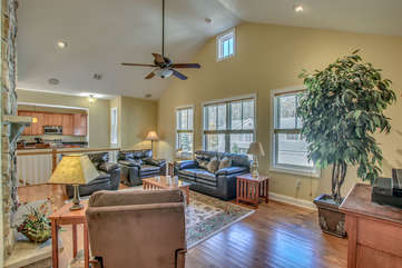 Upstairs Living Room with Fireplace, Couches, Armchair, and Ceiling Fan.