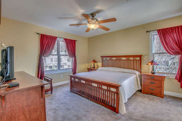 Large Bed Bedroom with Dresser and Two Nightstands, Table Lamps and Ceiling Fan.