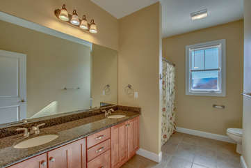 Double Sink Bathroom Vanity with Mirror, Toilet, and Shower.